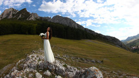 Woman in long white dress near mountain. Young bride in white dress holding bouquet with mountains in background Stock Photos