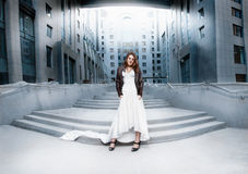 Woman in long white dress standing on stairs against modern building Royalty Free Stock Images