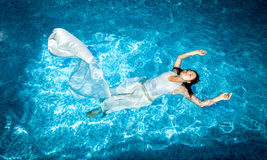 Woman in long white dress swimming in pool at sunny day Royalty Free Stock Image