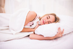 Woman with long white hair lying and sleeping in bed. Tender cute young woman with long white hair lying and sleeping in bed Stock Photo