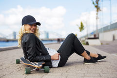 Woman with longboard sitting on the ground Royalty Free Stock Image
