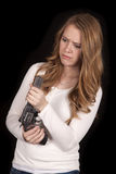 Woman look down at revolver curious. A woman holding on to her weapon confused Stock Photography