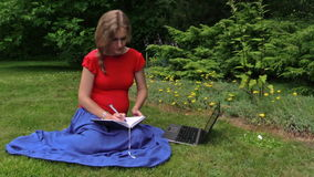Woman look for info about pregnancy in laptop, note down to book stock video footage