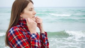 Woman look at sea waves on beach. Female traveler is cold during vacation on beach at stormy weather. Young woman looking at big sea waves on beach. Female stock footage