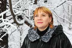 Woman look up in woods in snow. Red-headed woman dressed black jacket look up in woods in snow at winter Stock Image