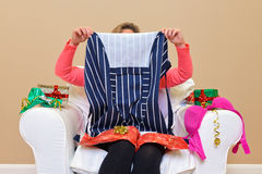 Woman - Look what I got for Christmas. A woman opening Christmas presents to discover she got an apron and some underwear Royalty Free Stock Images