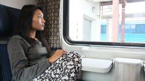 Woman look from window of train on railway station. Young woman look from window while traveling by train on railway station stock footage