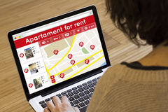 Woman lookin apartment for rent on her laptop Stock Photo