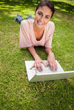 Woman looking ahead while using a laptop as she lies down in gra Stock Photography