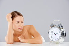 Woman looking at an alarm clock in consternation Stock Photo