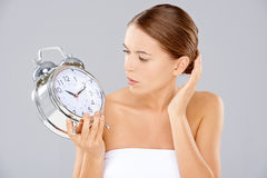 Woman looking at an alarm clock in consternation Stock Photography