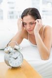 Woman looking at alarm clock while lying in bed Royalty Free Stock Photography