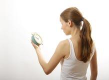 Woman looking at alarm clock Stock Photography