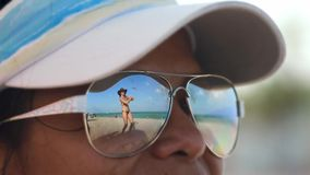 Woman looking at another woman dancing on beach through her sunglasses stock footage