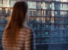 Woman looking at an apartment block Stock Image