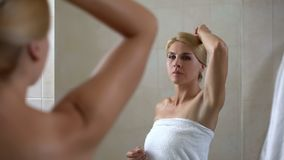 Woman looking at armpit, low quality depilation, bad smell, cheap antiperspirant royalty free stock photo