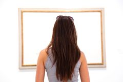 Woman looking at art painting in museum. Blank canvas Royalty Free Stock Image