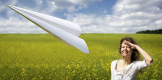 Woman looking after ascending paper plane Royalty Free Stock Image
