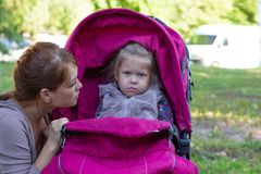 Free Woman Looking At Offended Little Girl Sitting In Stroller Stock Photos - 152204913