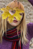 Woman looking through autumn leaf with heart shaped hole Stock Images