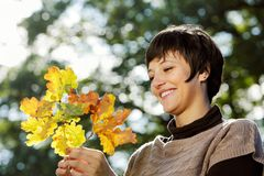 Woman looking at autumn leaves Royalty Free Stock Photos