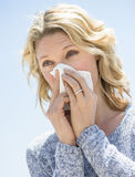 Woman Looking Away While Blowing Nose Against Clear Sky royalty free stock image