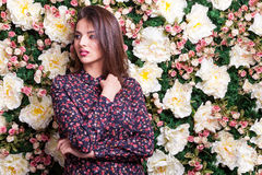 Woman looking away from camera on flower wall Stock Photography