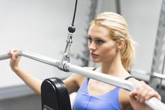 Woman Looking Away While Doing Weight Exercise At Club Stock Images