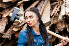 Woman looking away holding an ax in hand Royalty Free Stock Images