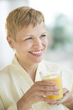 Woman Looking Away While Holding Glass Of Juice Stock Photo