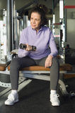 Woman Looking Away While Lifting Weight In Club. Full length of senior woman looking away while lifting weight in health club stock photos