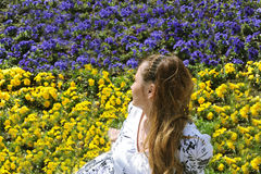 Woman looking away on meadow with yellow and blue flowers Stock Photos
