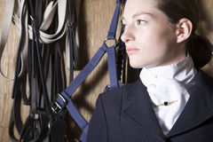 Woman Looking Away With Reins Hanging Behind. Closeup of a women looking away with reins hanging on wooden wall in background Stock Image