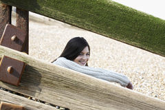 Woman Looking Away While Sitting Behind Balustrade At Beach Royalty Free Stock Photography