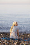 Woman Looking Away While Sitting On Blanket At Beach Royalty Free Stock Image
