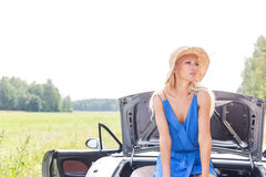 Woman looking away while sitting on convertible trunk against clear sky Royalty Free Stock Images