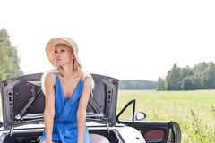 Woman looking away while sitting on convertible trunk against clear sky Stock Images