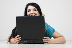Woman looking away and spy behind laptop Royalty Free Stock Photos