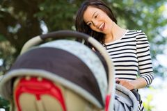 Woman Looking Into Baby Carriage In Park Royalty Free Stock Image