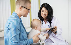 Woman Looking At Baby Grabbing Digital Tablet From Female Doctor Royalty Free Stock Photos
