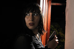 Woman looking back and holding a gun Stock Photography
