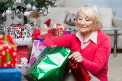 Woman Looking In Bag While Sitting By Christmas Royalty Free Stock Image