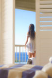 Woman looking from balcony. Back view through shutter doors of a young woman leaning on a railing, looking out over the ocean.  Soft focus applied Royalty Free Stock Image