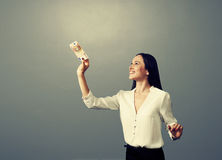 Woman looking at banknote over dark Royalty Free Stock Image