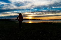 A woman looking away , River Background royalty free stock images