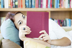 Woman looking from behind book Stock Photography