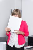 Woman is looking from behind a file Royalty Free Stock Photo