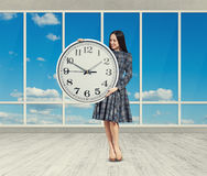 Woman looking at big clock Stock Image