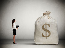 Woman looking at big money bag Royalty Free Stock Photo