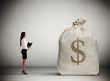 Woman looking at big money bag royalty free stock photo